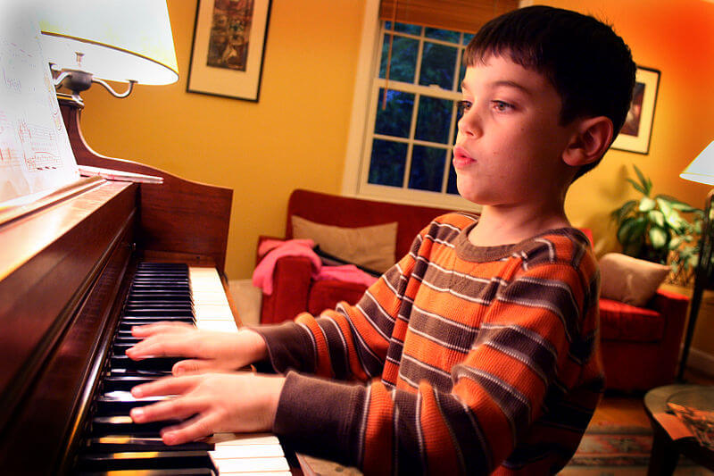 Photo of a young boy practicing piano