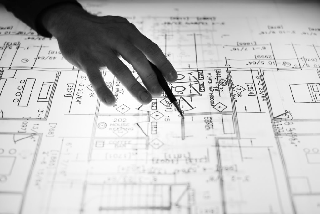 Handing holding pencil while pointing at elements of a blueprint for a house, in black and white